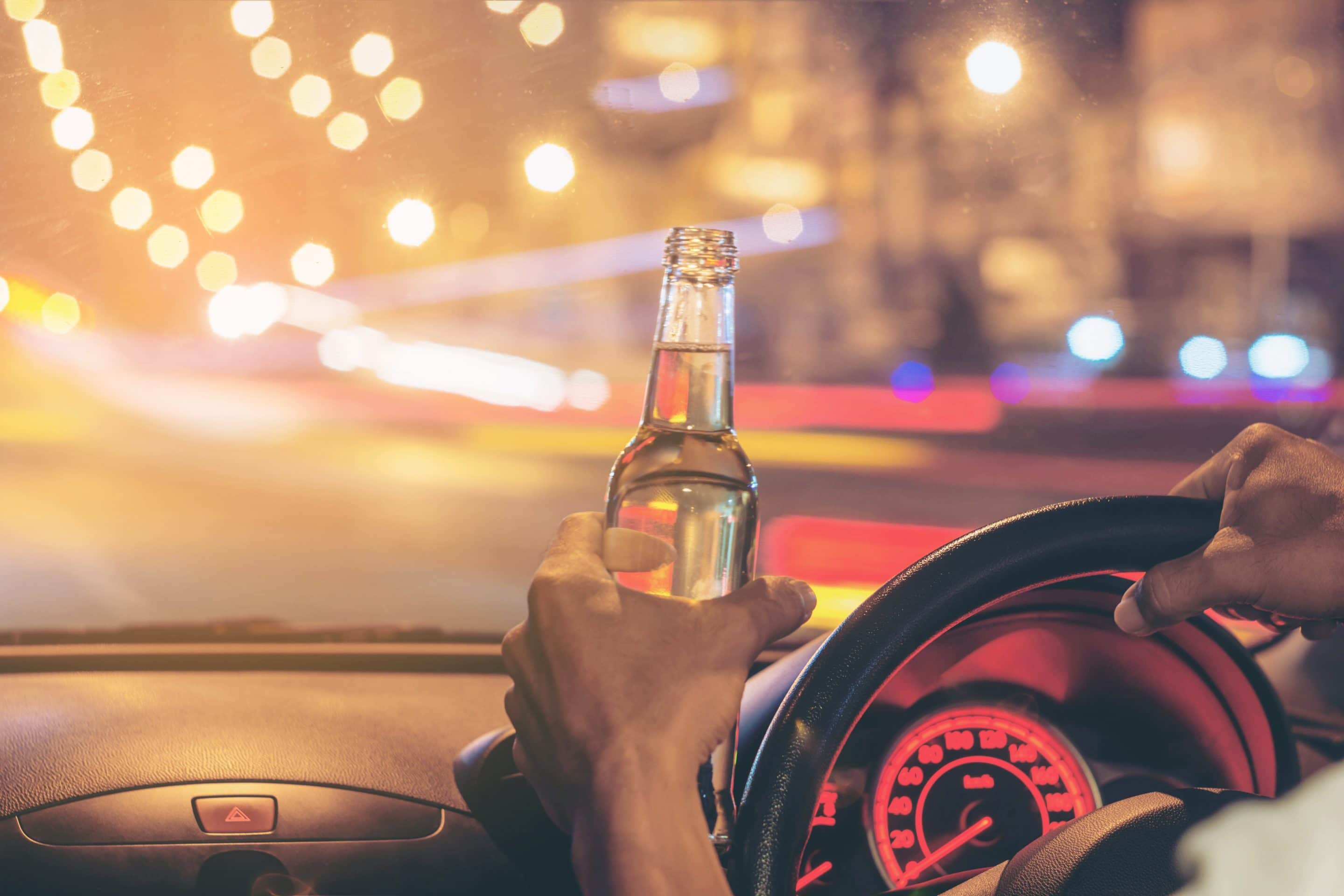 Drunk young man driving a car with a bottle of beer. Don't drink and drive concept. Driving under the influence. DUI, Driving while intoxicated.